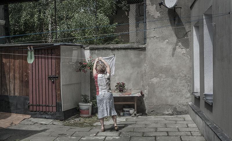 Livet går vidare. En kvinna hänger tvätt på gården där min farmor och farfar levde på 1930-talet.